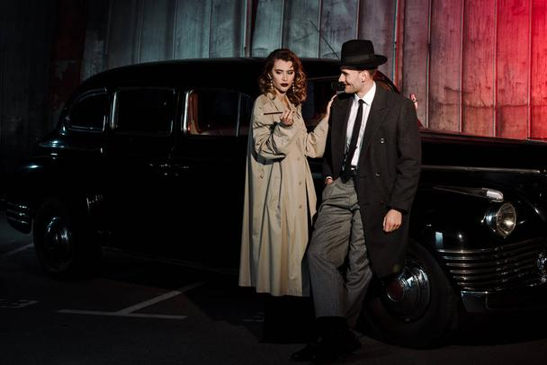 happy gangster in hat looking at woman with cigarette near retro car - Photo, Image