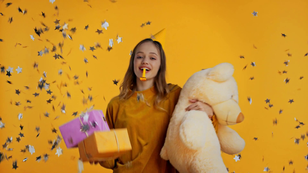 smiling teenager holding gifts and toy isolated on yellow - Footage, Video