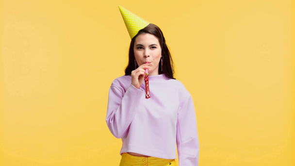 smiling girl in party cap blowing party horn and waving hand isolated on yellow - Footage, Video