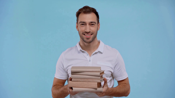 smiling man holding books isolated on blue - Footage, Video