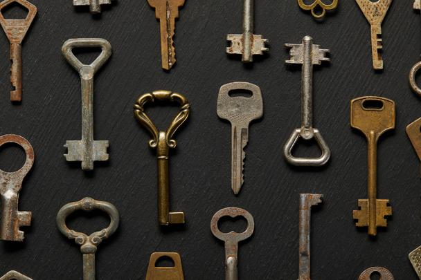 top view of vintage rusty keys on black background - Photo, Image