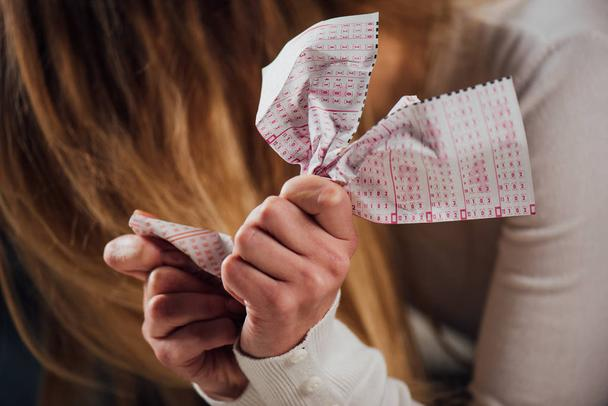 selective focus of upset woman crumpling lottery ticket while sitting with bowed head - Photo, Image