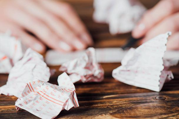 selective focus of crumpled lottery tickets near gambler marking numbers in lottery card on wooden table - Photo, Image