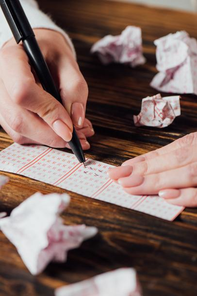 partial view of gambler marking numbers in lottery ticket near crumpled lottery cards on wooden table - Photo, Image
