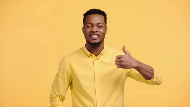 happy african american man showing thumb up isolated on yellow - Footage, Video