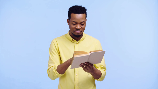 smiling african american man reading book isolated on blue - Footage, Video