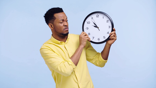 sad african american man looking at clock isolated on blue - Footage, Video