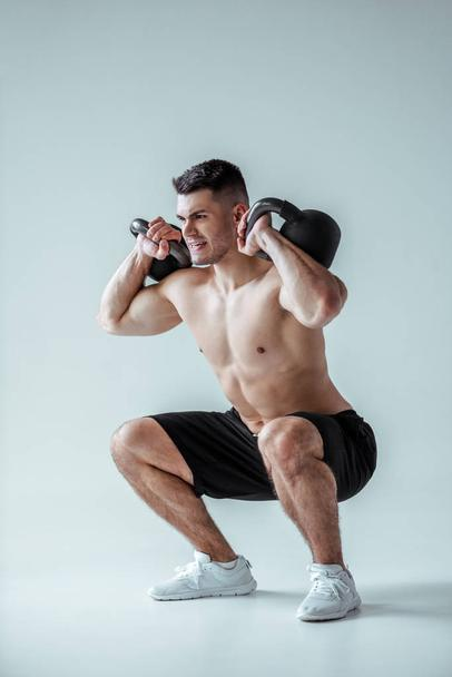 sexy muscular bodybuilder with bare torso squatting with kettlebells on grey - Photo, Image