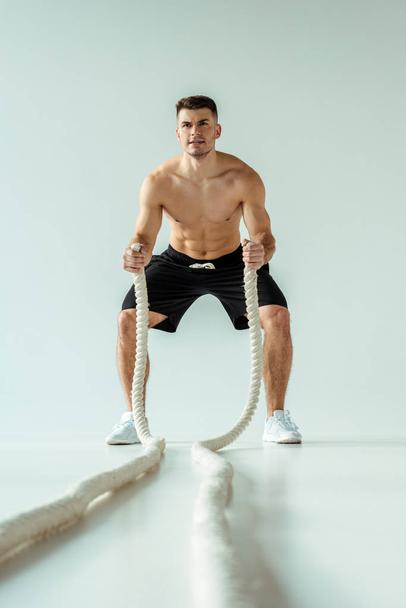 selective focus of sexy muscular bodybuilder with bare torso exercising with battle rope on grey background - Photo, Image