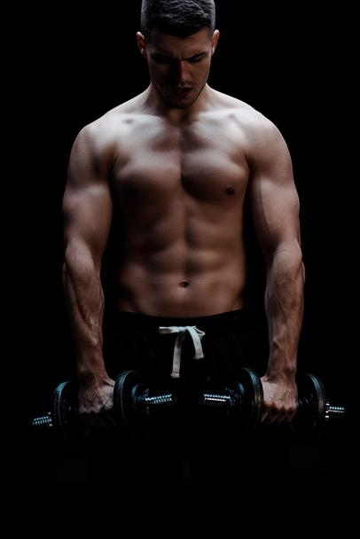sexy muscular bodybuilder with bare torso excising with dumbbells isolated on black - Photo, Image