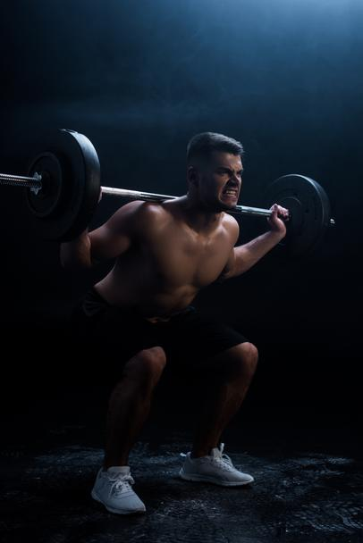 tense sexy muscular bodybuilder with bare torso squatting with barbell on black background - Photo, Image