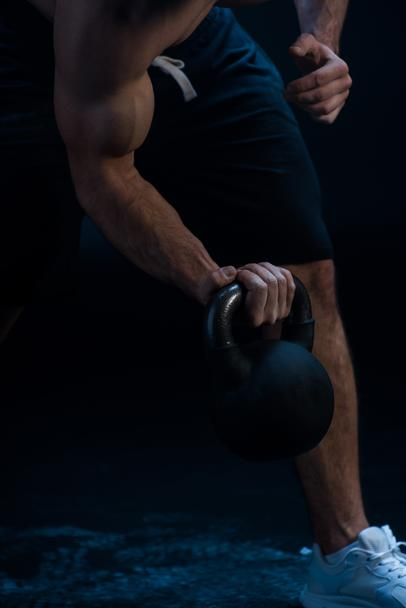 cropped view of sexy muscular bodybuilder excising with kettlebell on black background - Photo, Image