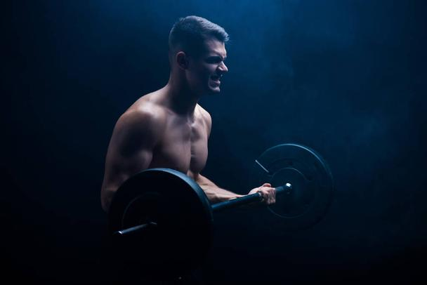 tense sexy muscular bodybuilder with bare torso excising with barbell on black background - Photo, Image