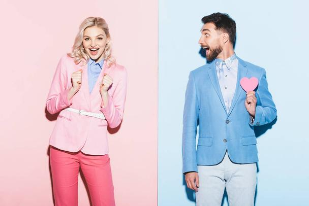 shocked woman and handsome man with heart-shaped card on pink and blue background  - Photo, Image