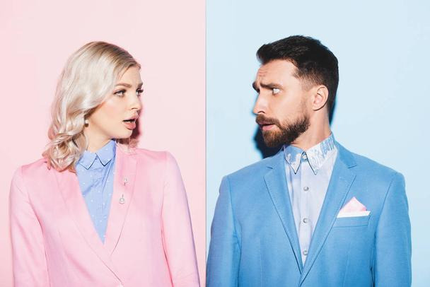 shocked woman and handsome man looking at each other on pink and blue background  - Photo, Image