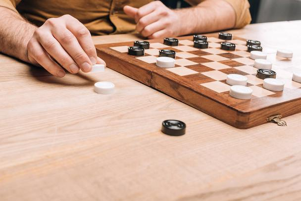 Cropped view of man holding checker by checkerboard on table - Photo, Image