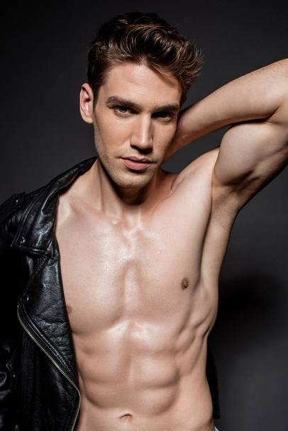 sexy young man with muscular torso putting on biker jacket on black background - Photo, Image