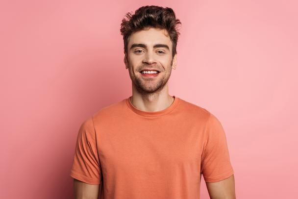 handsome, happy man smiling at camera on pink background - Photo, Image