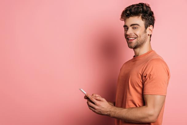 cheerful young man smiling at camera while chatting on smartphone on pink background - Photo, Image