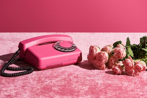 roses and vintage phone on velour pink cloth isolated on pink, girlish concept - Photo, Image