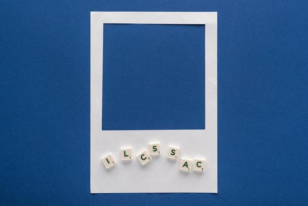 top view of letters on cubes and white photo frame on blue background - Photo, Image