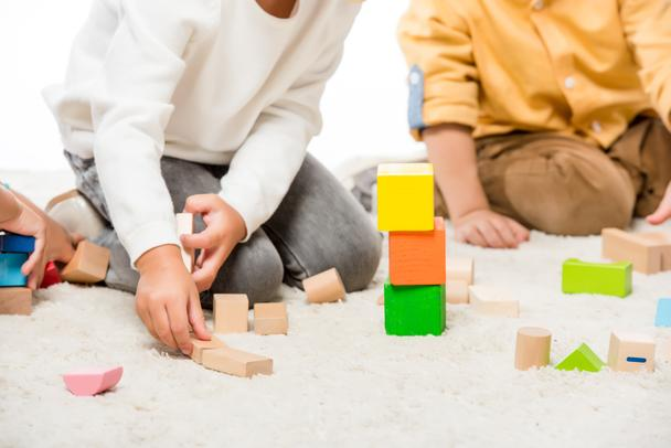 cropped view of kids playing with wooden blocks on carpet - Photo, Image