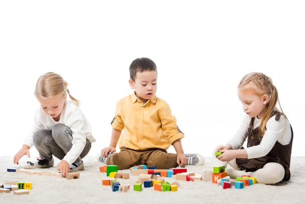 multiethnic kids playing with wooden blocks on carpet, isolated on white - Photo, Image