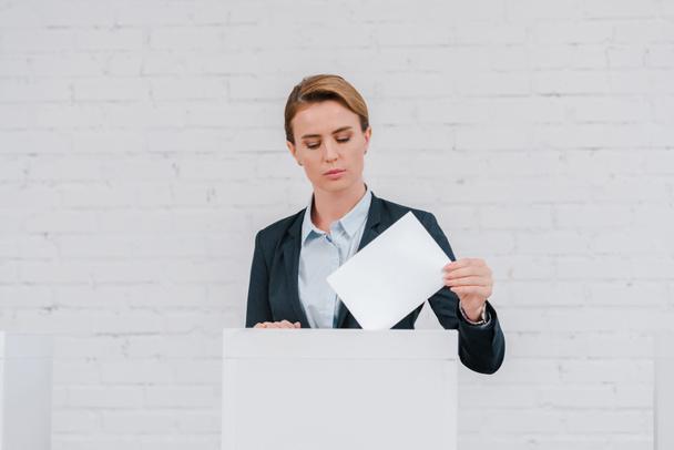attractive businesswoman voting near brick wall  - Photo, Image