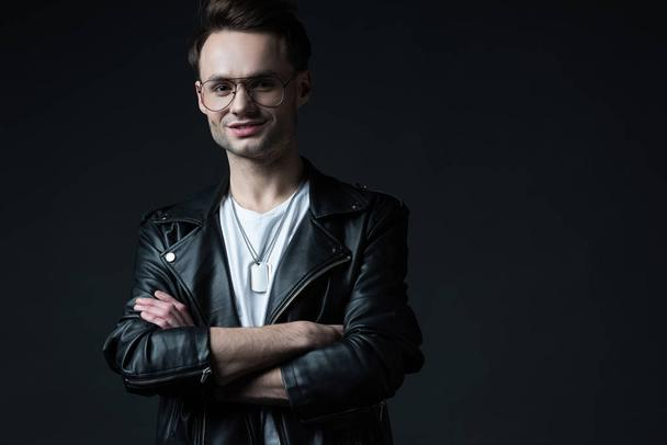smiling stylish brutal man in biker jacket with crossed arms isolated on black - Photo, Image
