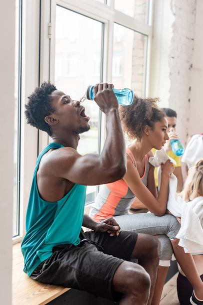 Side view of multicultural dancers drinking water while resting in dance studio - Photo, Image