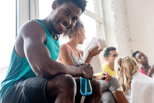Selective focus of african american dancer holding sports bottle while smiling at camera in dance studio - Photo, Image