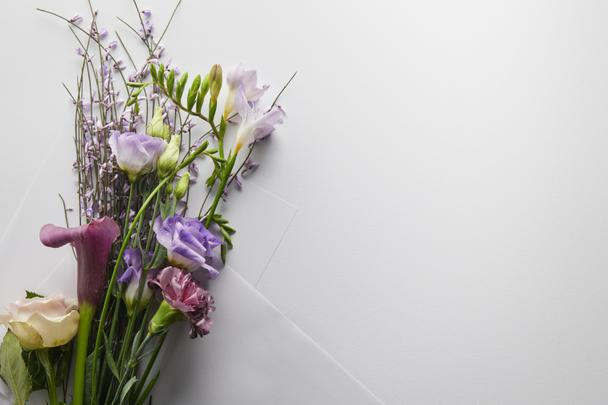 top view of violet bouquet wrapped in paper on white background - Photo, Image