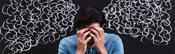 panoramic shot of frustrated young man with steam drawing on chalkboard behind - Photo, Image