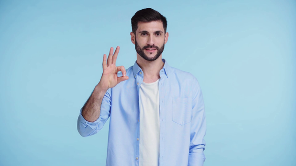 happy man showing ok sign isolated on blue  - Footage, Video