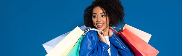 Усміхаючись африканською американською жінкою з сумками, відокремленими від синього, панорамного пострілу. - Фото, зображення