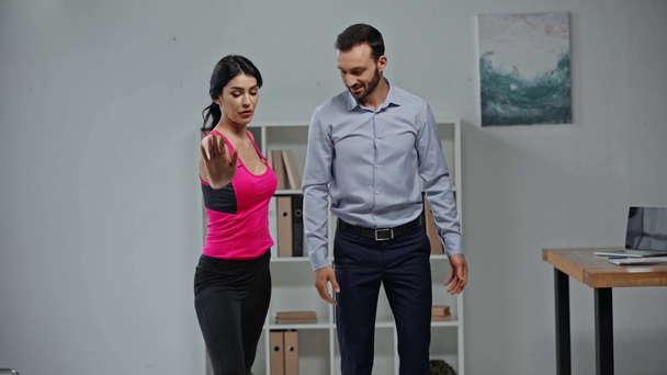 attractive fitness trainer instructing businessman doing exercising in office  - Footage, Video