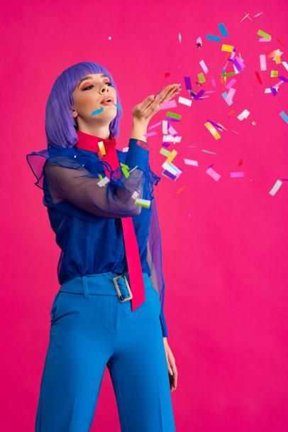 приваблива дівчина з поп-арту в пурпуровій перуці, що пускає конфетті, ізольована на рожевому - Фото, зображення