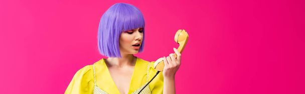 panoramic shot of beautiful emotional girl in purple wig holding retro telephone, isolated on pink - Photo, Image