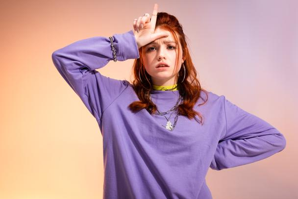 redhead female teenager in bad mood showing loser sign, on purple and beige  - Photo, Image