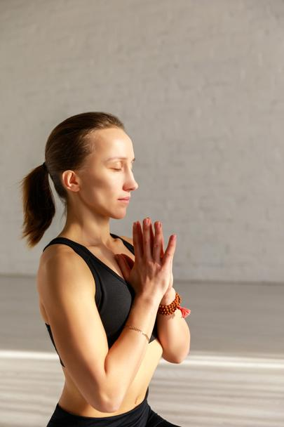 attractive woman with closed eyes and praying hands in yoga studio  - Photo, Image