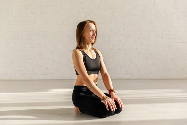 beautiful woman doing seiza exercise on floor in yoga studio  - Photo, Image