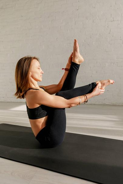 side view of woman with closed eyes stretching legs while sitting on yoga mat  - Photo, Image