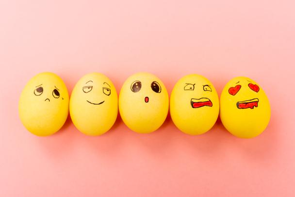 Top view of painted Easter eggs with different facial expressions on pink background - Photo, Image