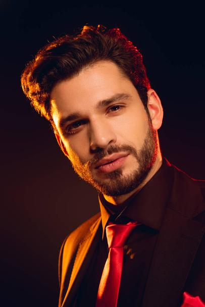 Handsome man in formal wear and red tie looking at camera isolated on black - Photo, Image