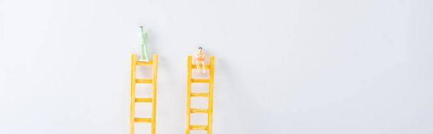Panoramic shot of two people figures on ladders on white background, concept of equality rights  - Photo, Image