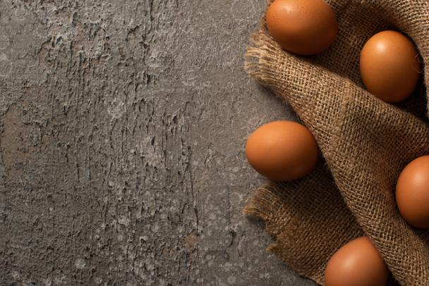 top view of brown eggs on sackcloth on grey textured background - Photo, Image