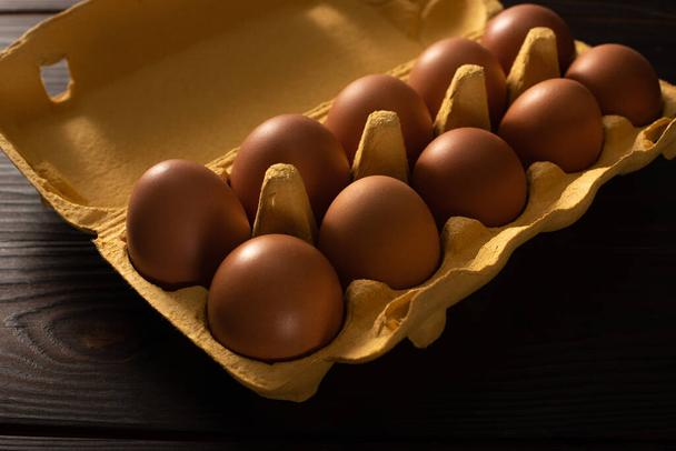 brown chicken eggs in egg tray on brown wooden background - Photo, Image