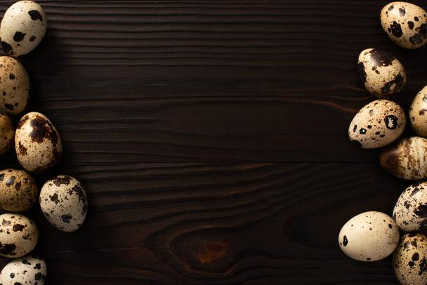 top view of quail eggs on brown wooden background - Photo, Image