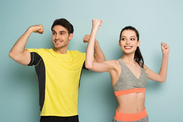 happy athletic couple standing in sportswear showing muscles on blue - Photo, Image