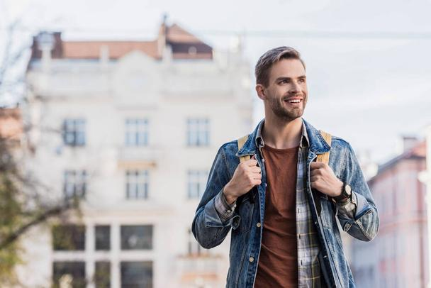 Handsome man with backpack smiling in city  - Photo, Image